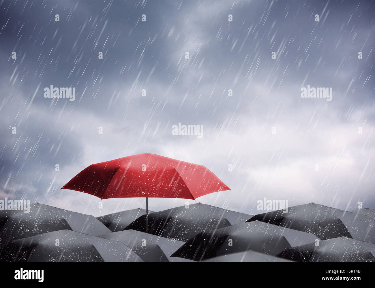 Black and one red umbrellas under rain and thunderstorm Stock Photo