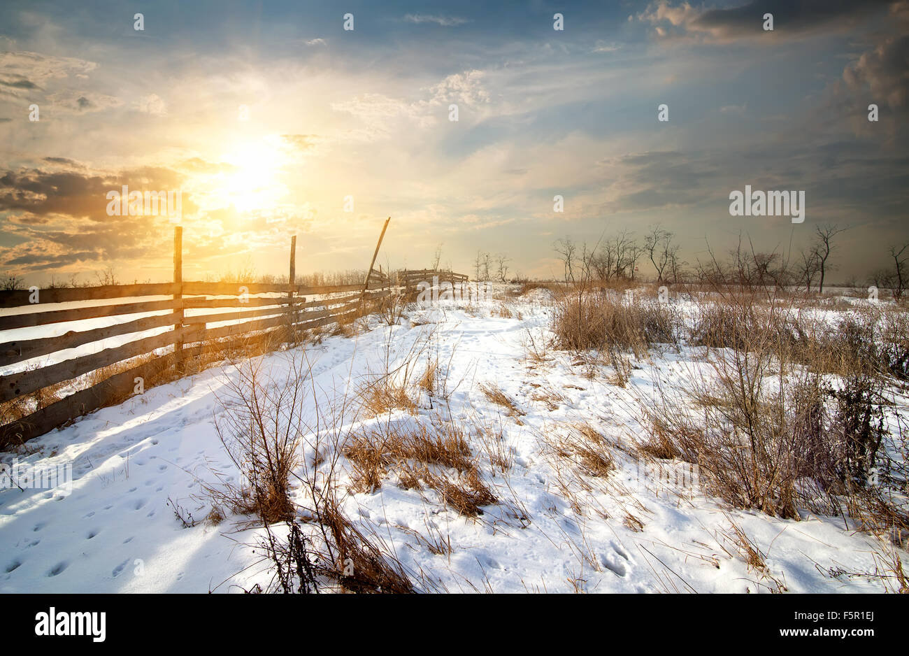 Wooden fence in winter field at sunset - Stock Image