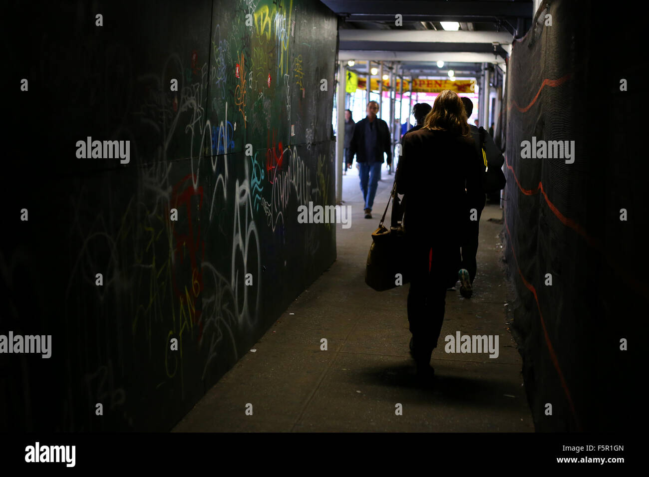 People, commuters walk through a dimly lit, narrow passageway at a New York City construction site - Stock Image