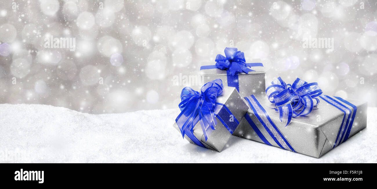 Silver Christmas Or Birthday Gift Boxes With Red Bows In Snow With