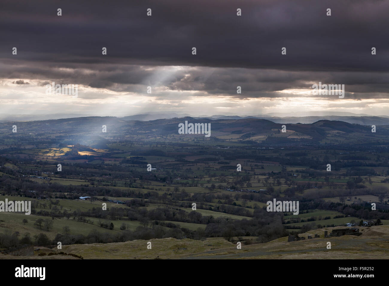 Crepuscular rays break through the clouds lighting up fields across Shropshire, from Clee Hill looking towards Wales Stock Photo