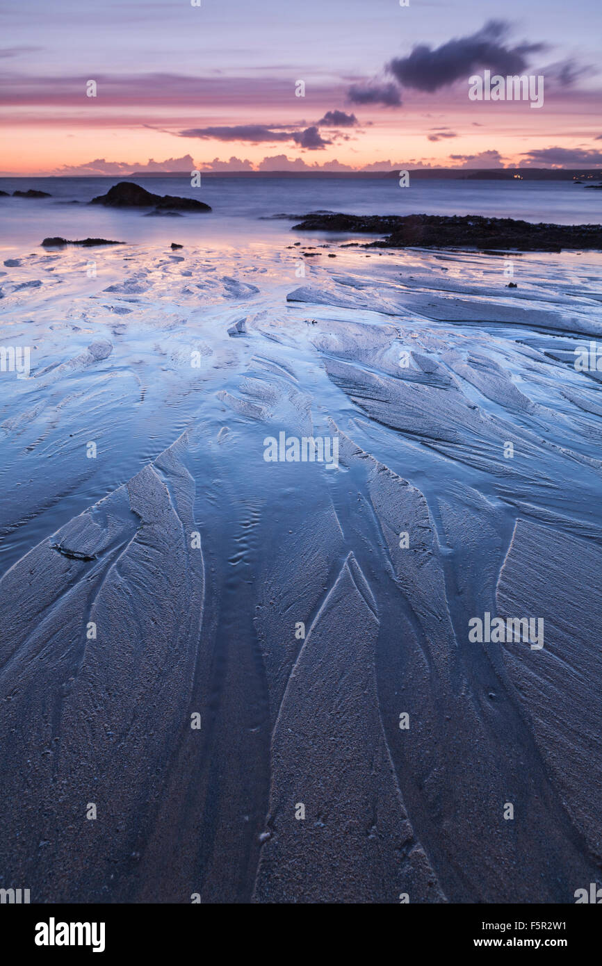 Sand patterns on Mouthwell beach created by the receding tide at sunset, Hope Cove, Devon. Stock Photo