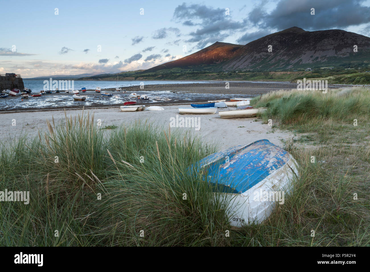Rowing boats are moored up on the shore of Caernarfon Bay near Trefor, The sun lights up Bwlch Mawr. Stock Photo