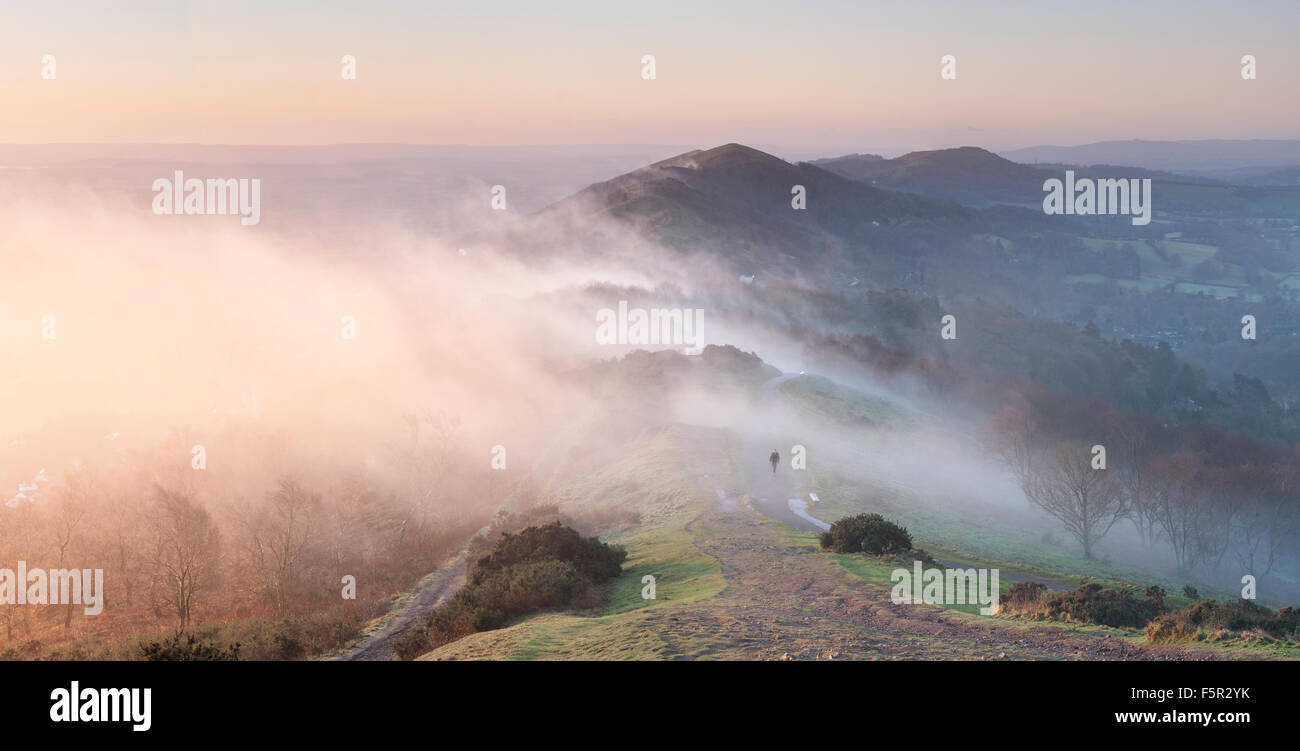 A lone walker is walking along the path to Summer Hill, Malvern Hills. The sunrise is turning the low cloud orange. Stock Photo