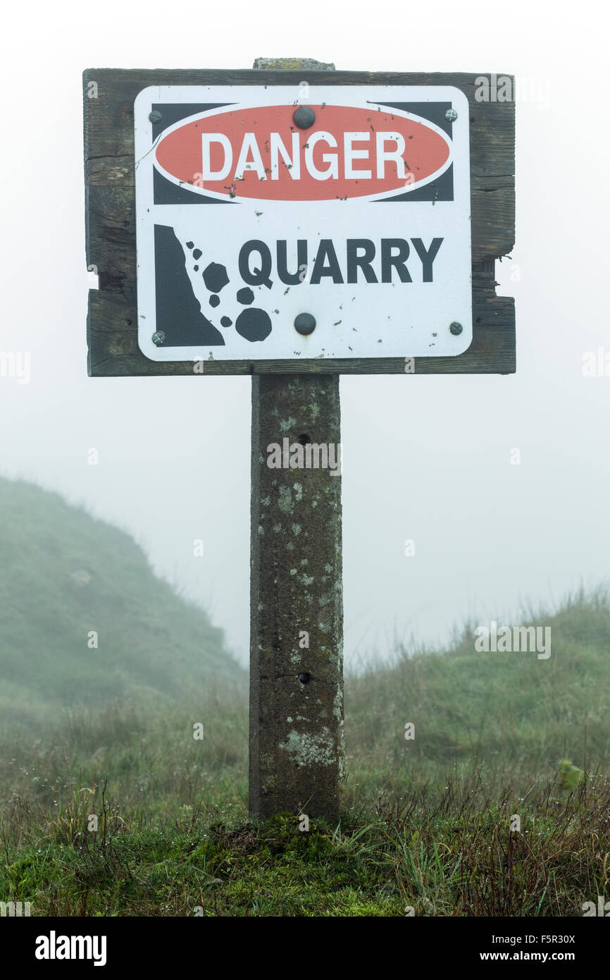 A Danger Quarry sign is positioned above a quarry in Malvern, Worcestershire. Stock Photo