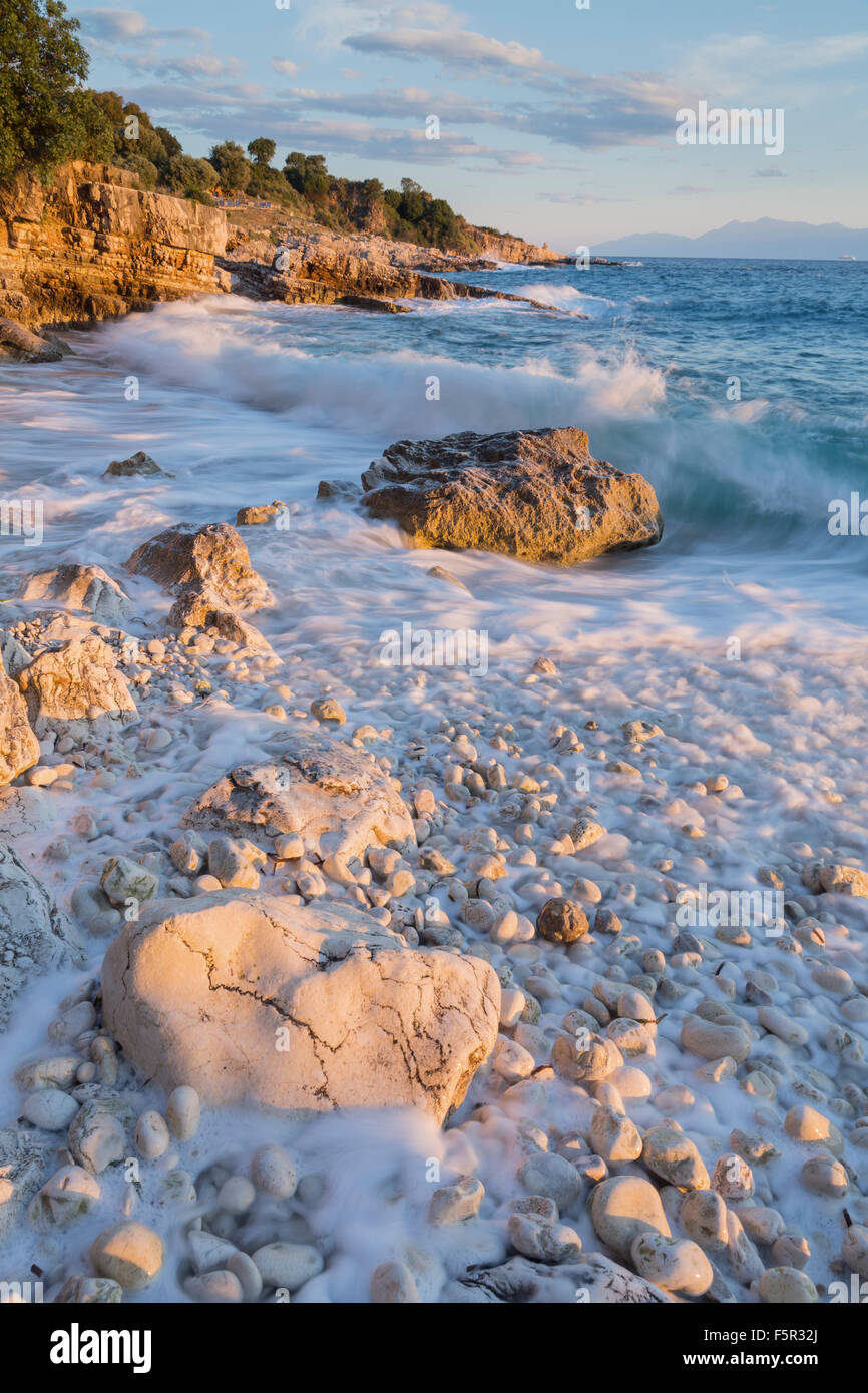 The pebbles and rocks on Bataria beach, Kassiopi, Corfu are lit up with the stong orange light of sunrise. Stock Photo