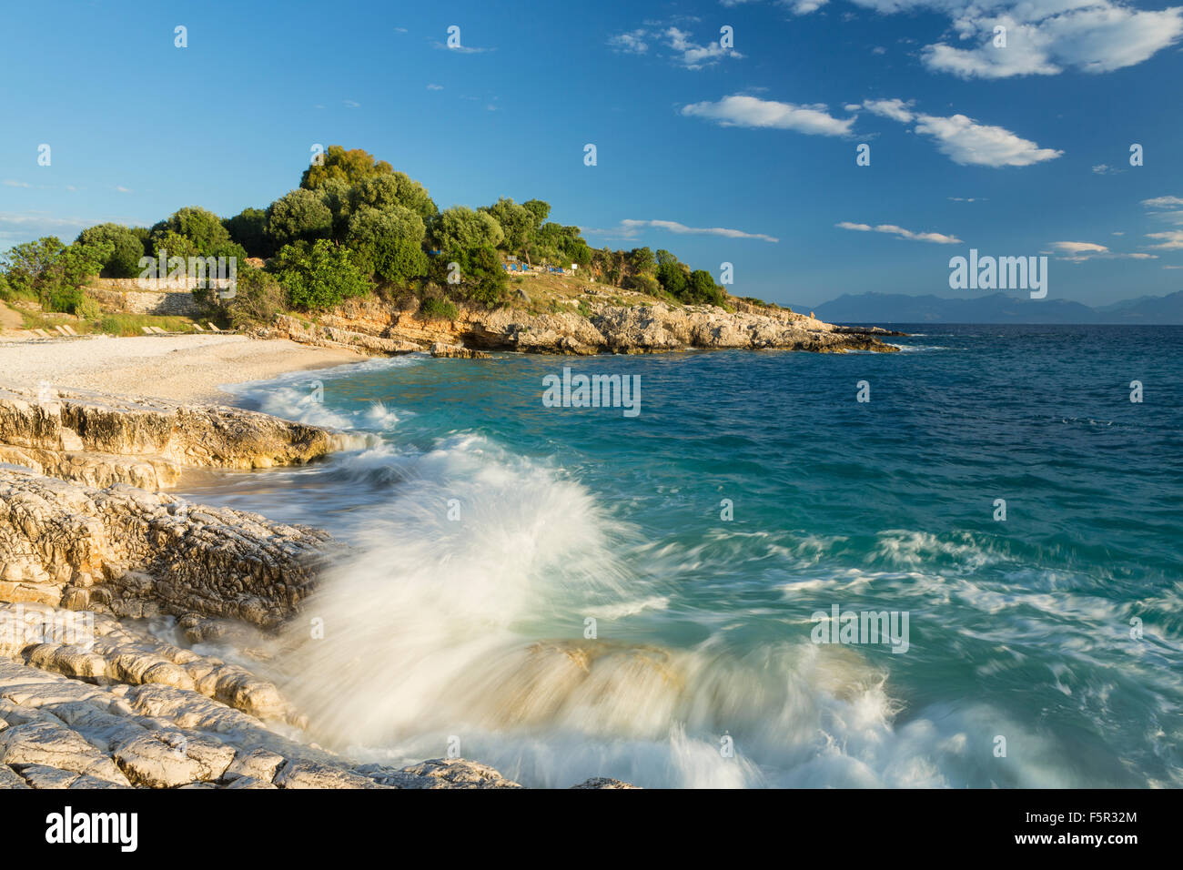 A wave crashes over the rocks on Batariaand Kanoni beach, Kassiopi, Corfu. The mountains of Albania can be seen Stock Photo