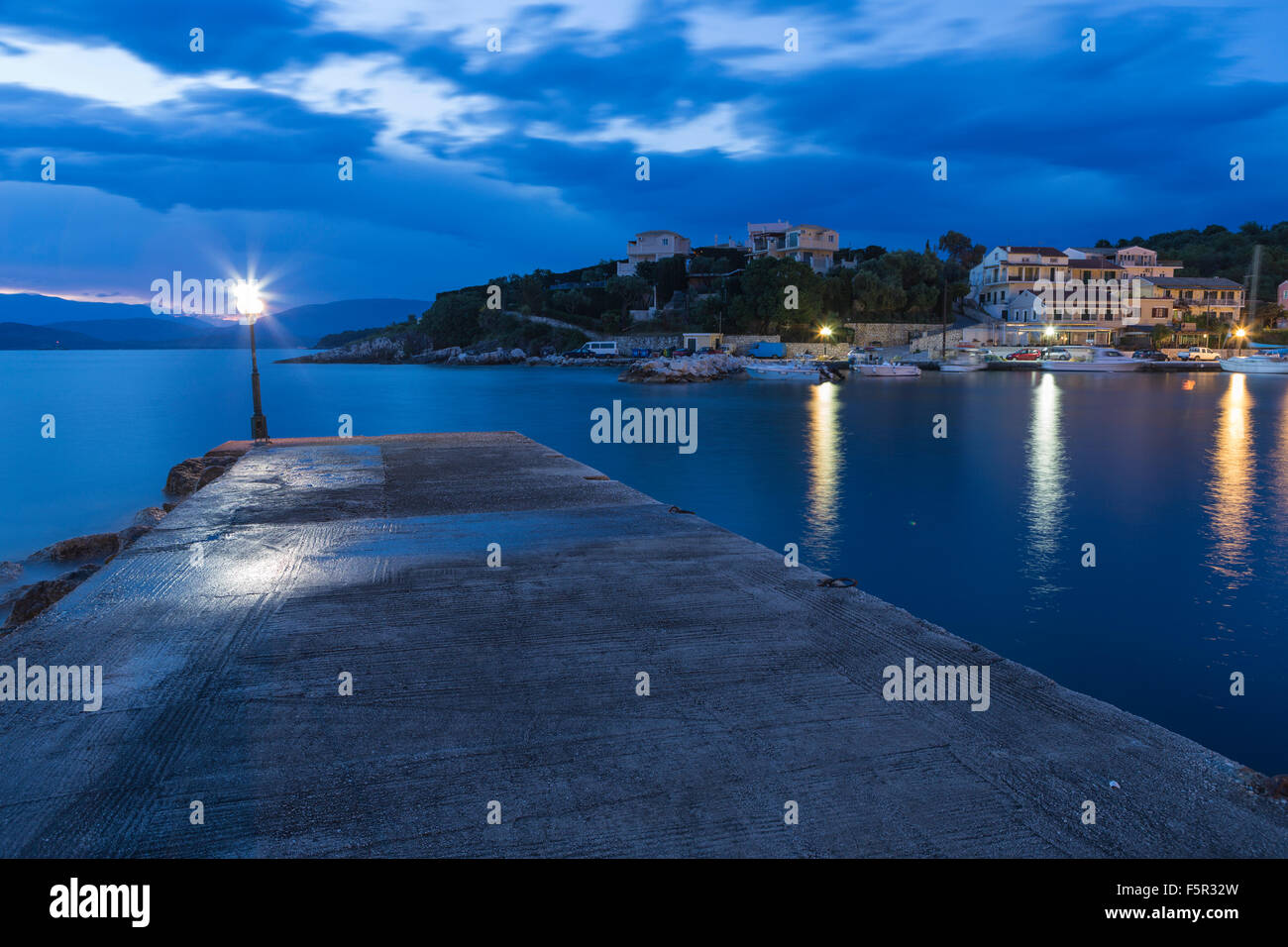 The harbour wall at Kassiopi in the morning light. A blue cast covers the water and sky with the occasional orange Stock Photo