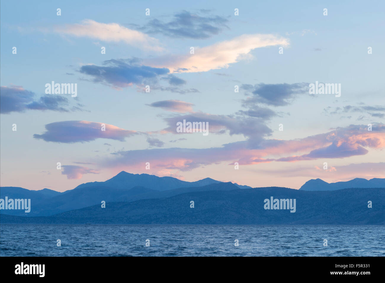 The clouds above the Mountains of Albania are coloured by the sunrise over the coast and Straits of Corfu at Kassiopi Stock Photo