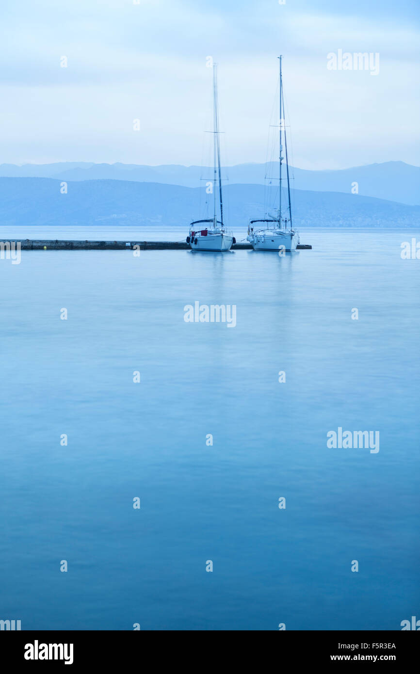 Two yatchs moored in Kassiopi Harbour in the cool blue morning light. - Stock Image