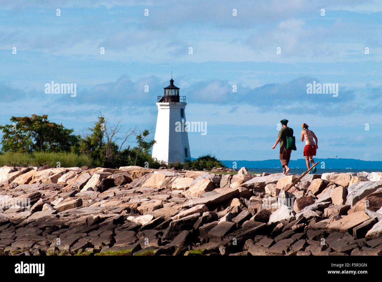 Hiking to Black Rock Harbor light along the mile-long jetty, in Bridgewater, Connecticut. Stock Photo