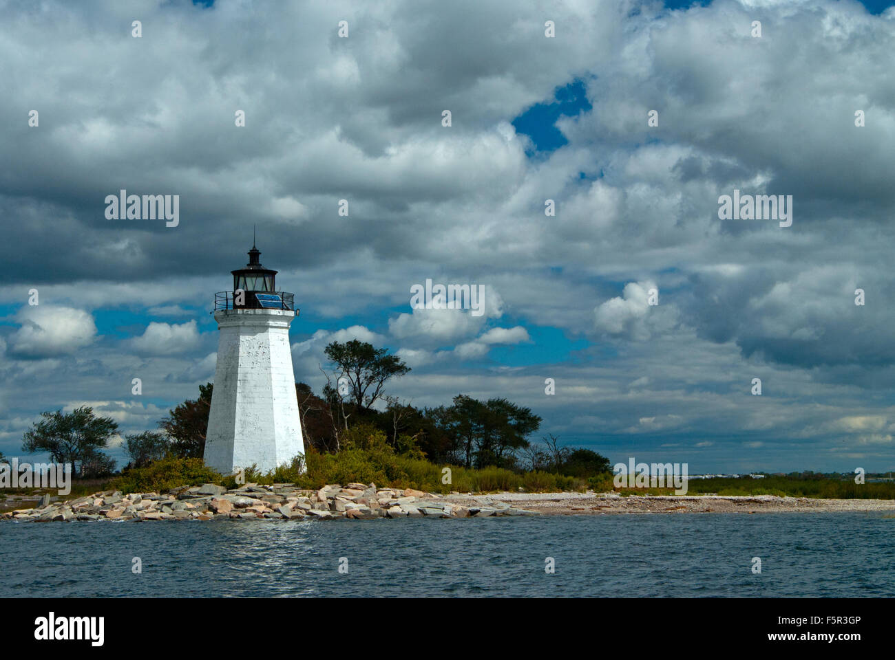 Sun breaks through clouds to illuminate Black Rock Harbor lighthouse tower in Bridgewater, Connecticut. It is also Stock Photo