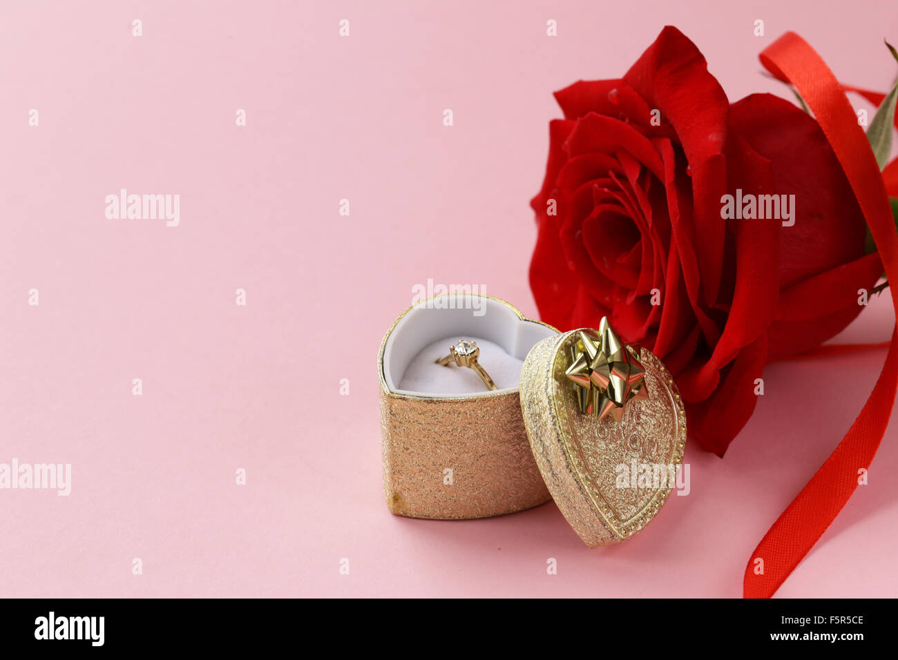 red rose flower with a gold ring with a diamond Stock Photo ...