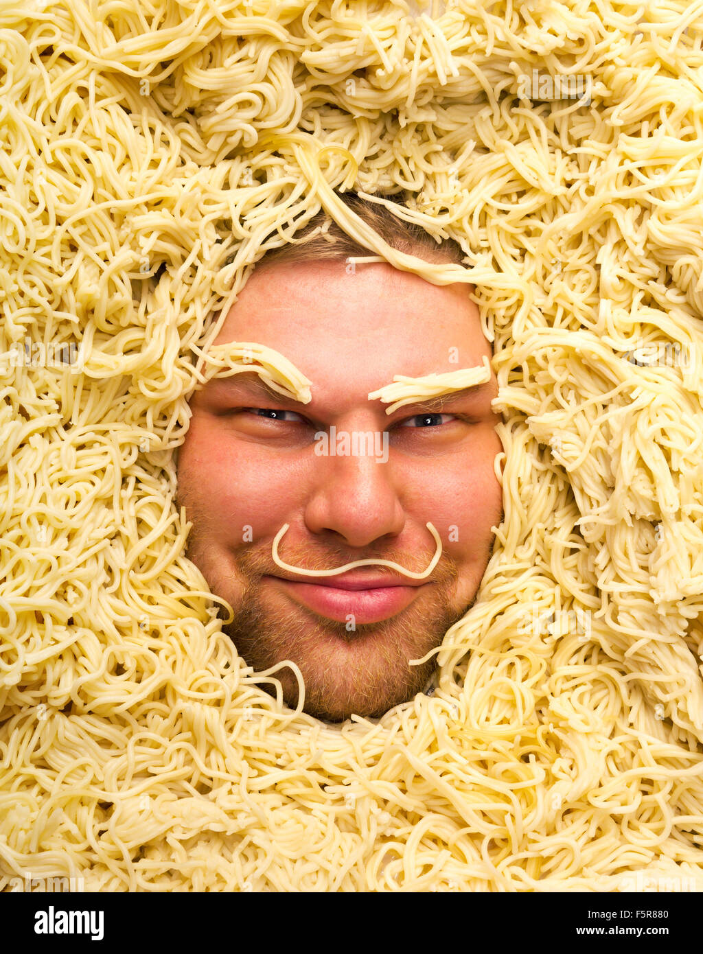 Happy man's face in pasta, closeup - Stock Image