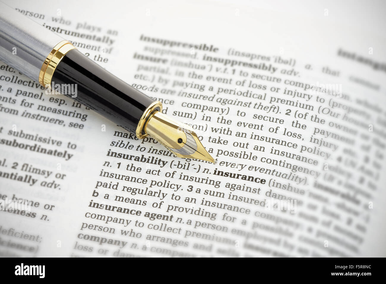 Fountain pen pointing to the word 'insurance' on the page of a generic dictionary. - Stock Image
