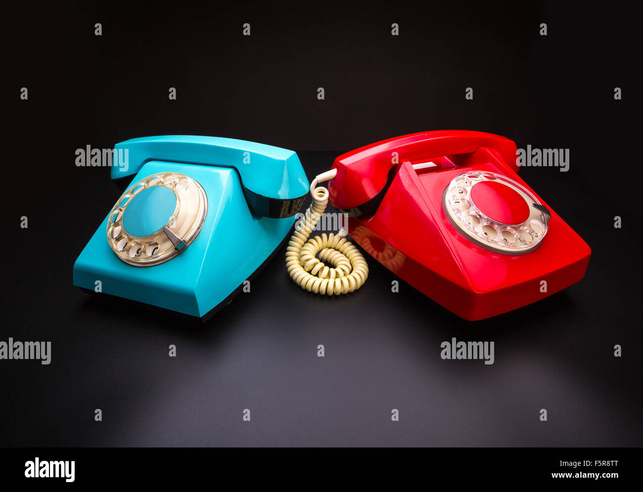 Vintage red and blue telephones side by side - Stock Image