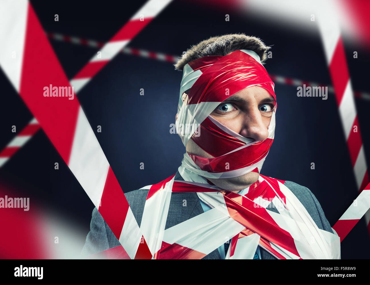Scared man with stripped duct tape over body - Stock Image
