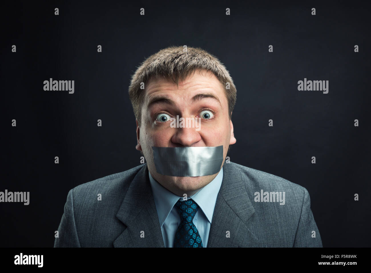 Young man with mouth covered by masking tape preventing speech, studio shoot - Stock Image