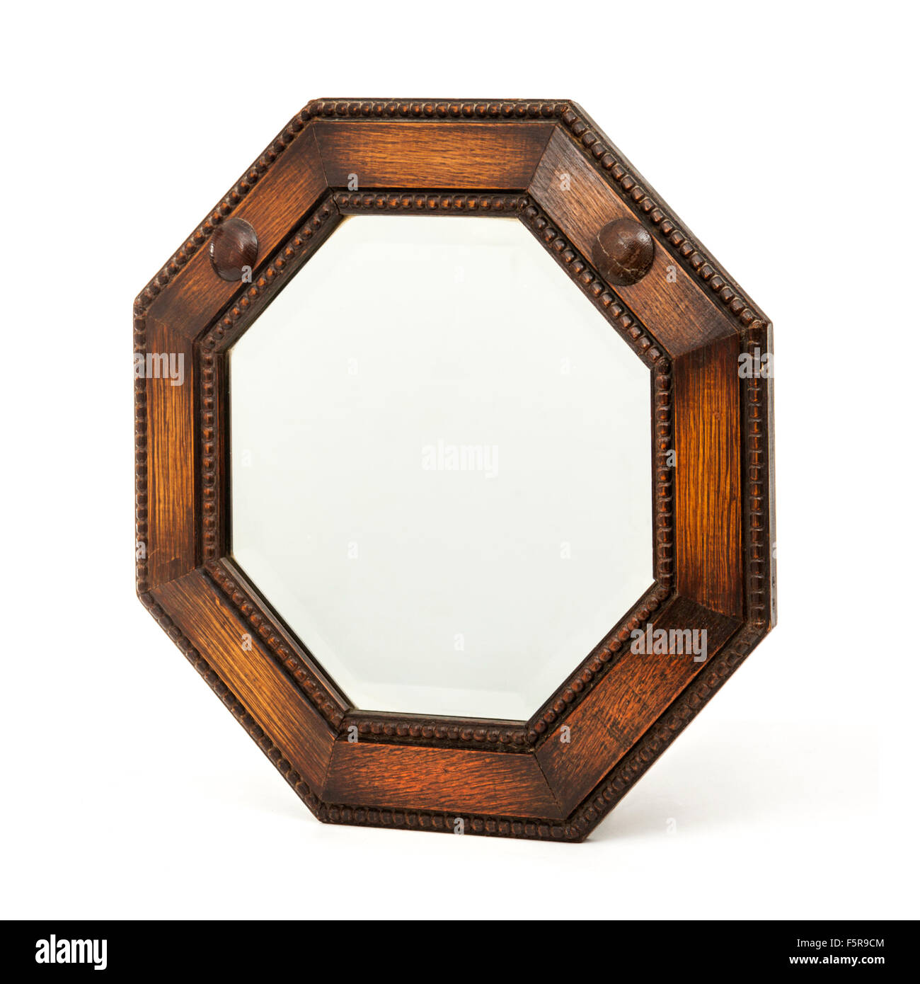 Antique octagonal wooden mirror with bevelled glass - Stock Image