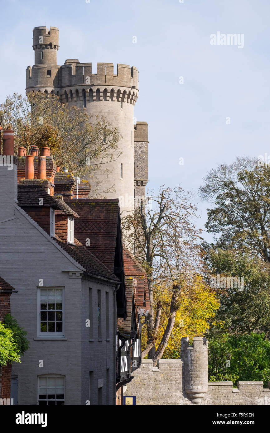 View showing the turrets of Arundel castle overpowering buildings in maltravers street Arundel west sussex UK - Stock Image