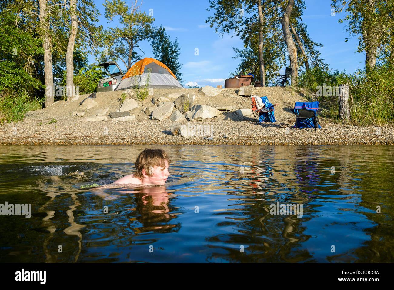 Boy swims in water at lake shore campsite,sẁiẁs Provincial Park, Osoyoos, British Columbia, Canada - Stock Image