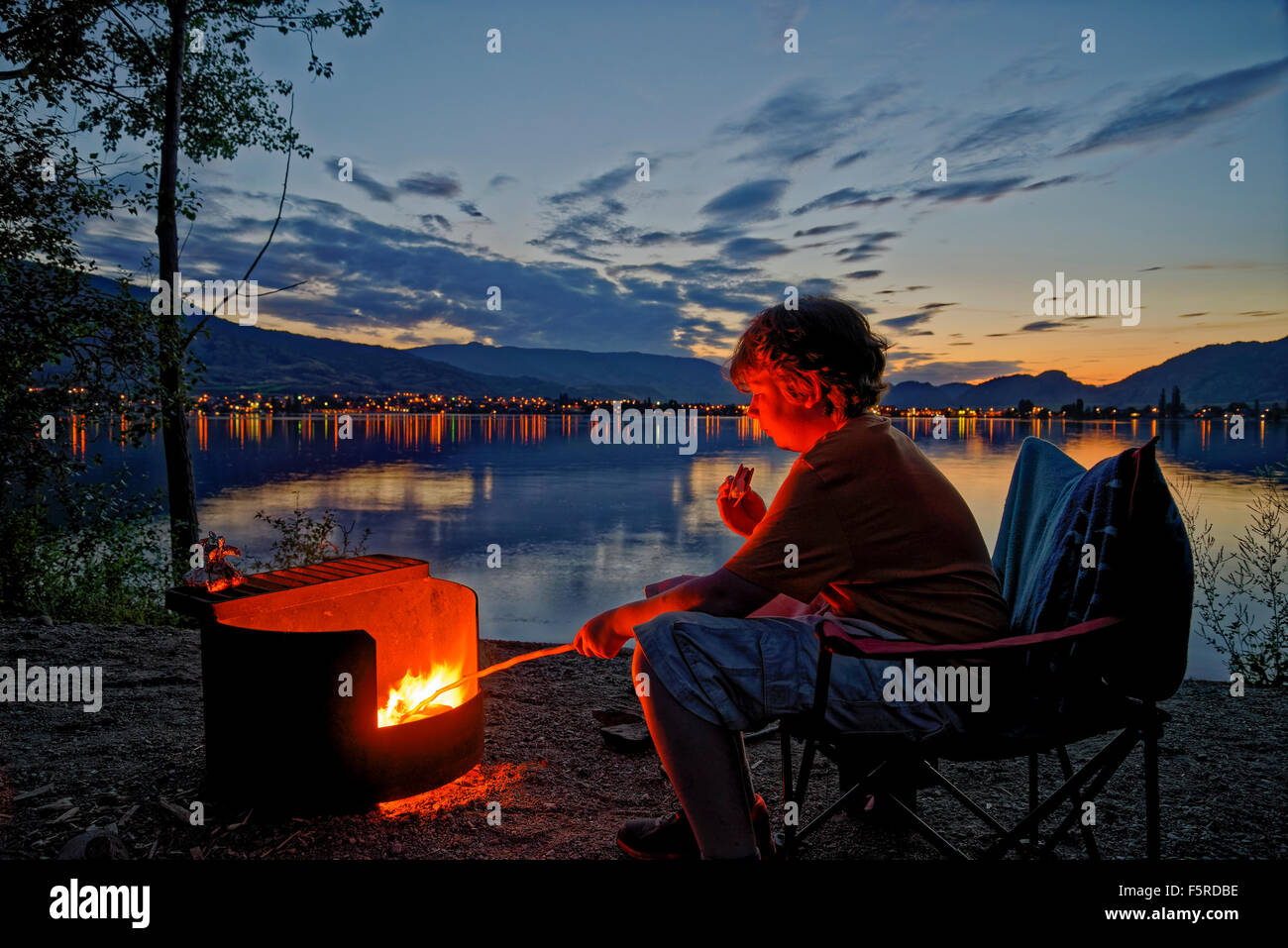 Boy roasts marshmallow in campfire at lakeshore campsite, sẁiẁs  Provincial Park, Osoyoos, British Columbia, Canada Stock Photo