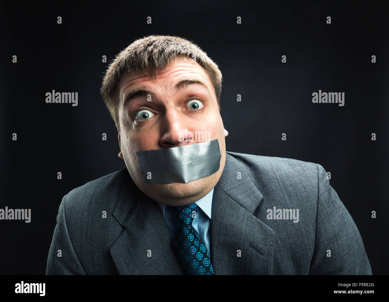 Surprised man with mouth covered by masking tape preventing speech, studio shoot - Stock Image