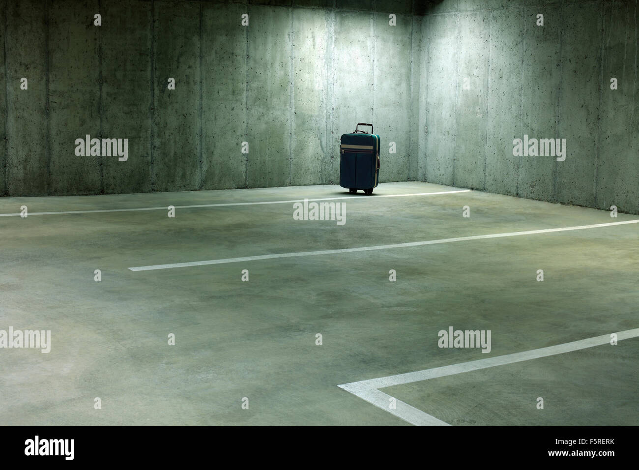 Forgotten Suitcase in Empty Parking Garage - Stock Image