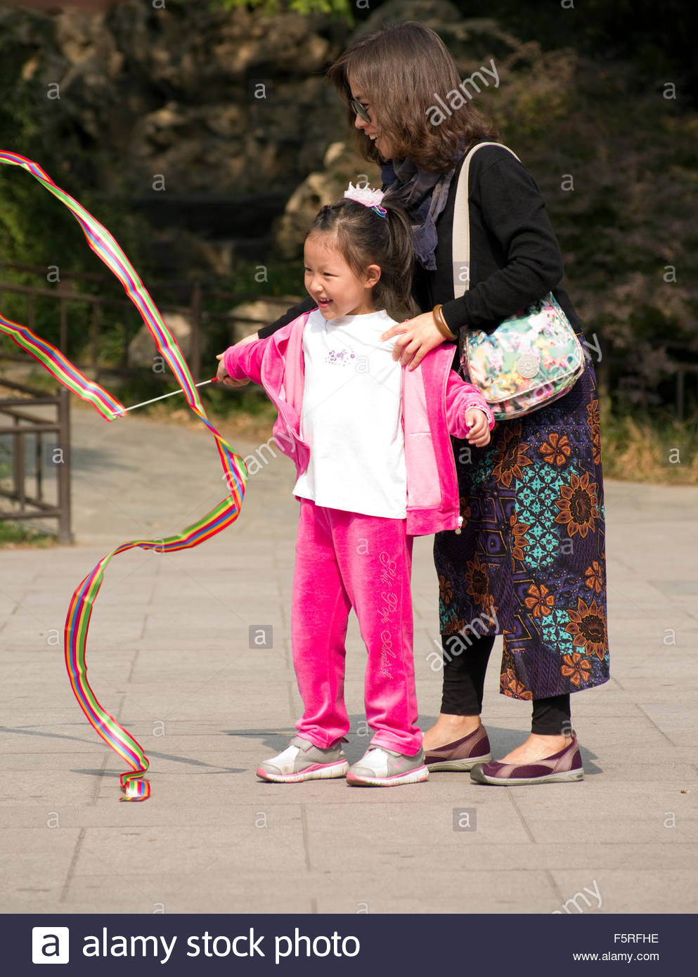 A young Chinese girl, happy to be twirling a ribbon with her mother, in Beihai Park in Beijing, China. - Stock Image