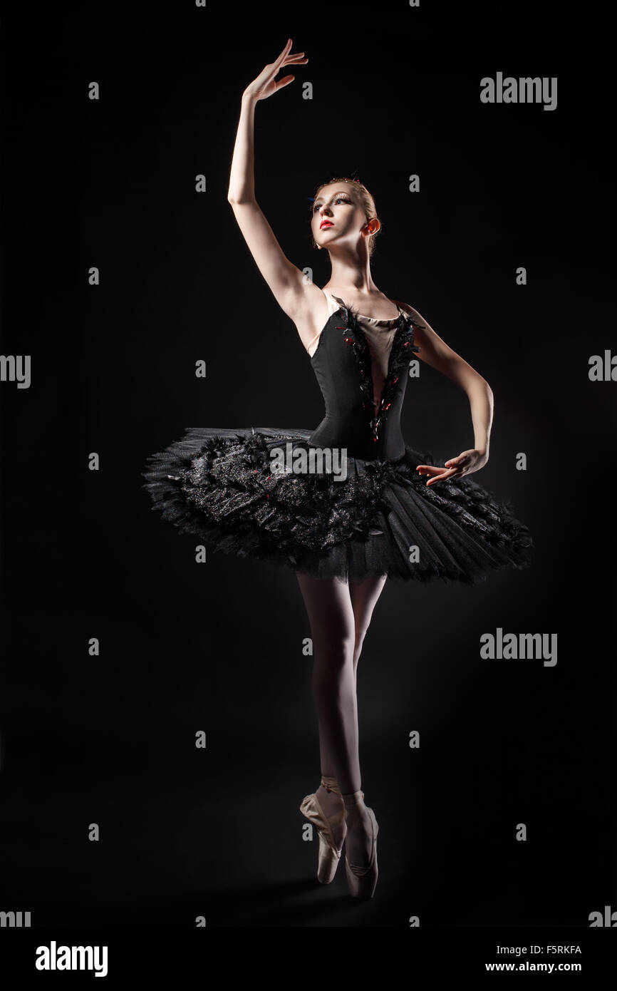Slim ballerina in a black corset and black tutu. Rehearsal in the theater. Classical Ballet. - Stock Image