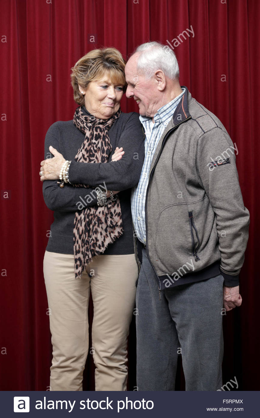 intimate portrait of senior man with younger woman - Stock Image