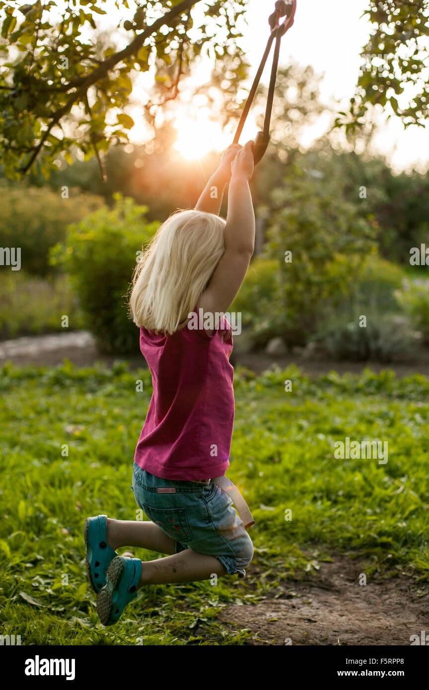 Sweden, Skane, Osterlen, Girl (4-5) swinging - Stock Image