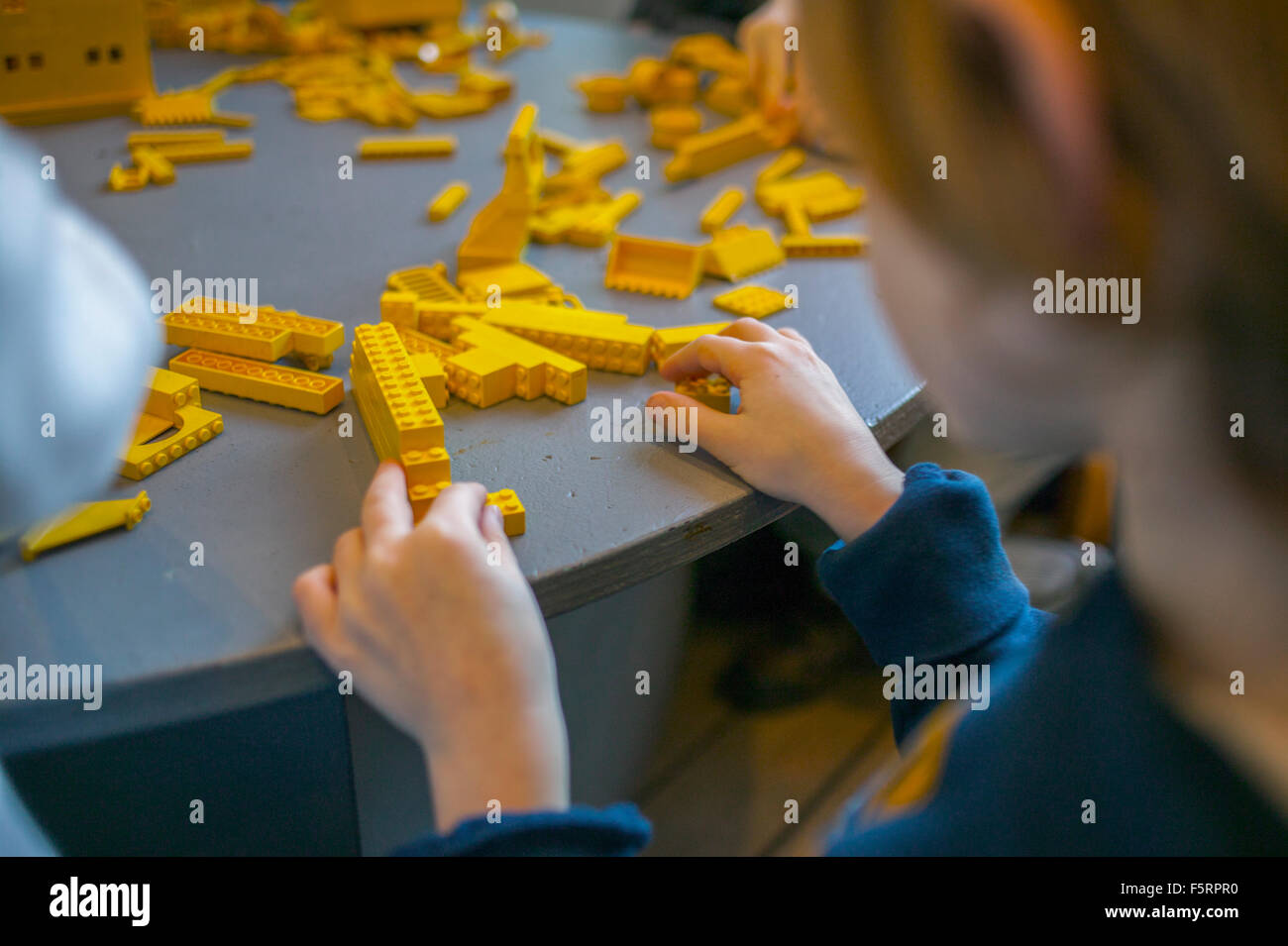 Sweden, Vastergotland, Lerum, Boy (8-9) playing with toy blocks - Stock Image