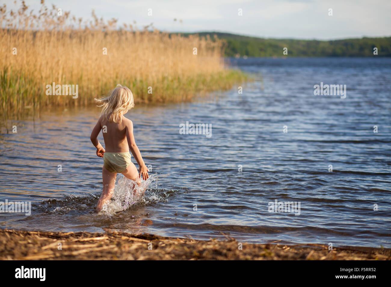Sweden, Vastergotland, Lerum, Lake Aspen, Girl (6-7) running into water - Stock Image