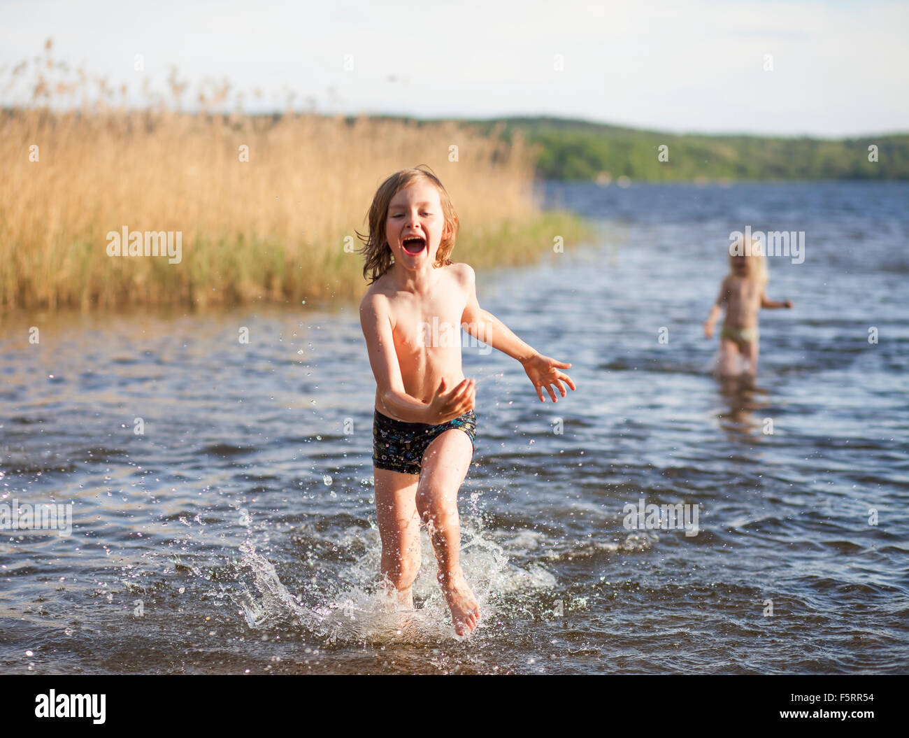 Sweden, Vastergotland, Lerum, Lake Aspen, Boy (8-9) and girl (6-7) playing in lake - Stock Image