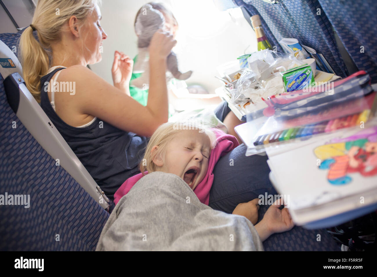 Sweden, Woman with yawning child on plane - Stock Image