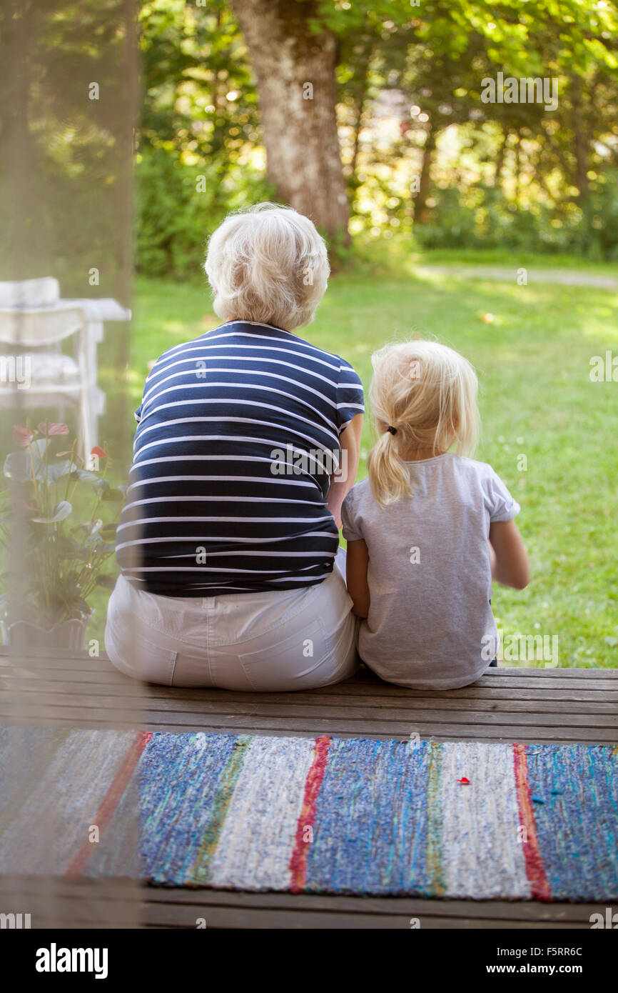 Sweden, Narke, Filipshyttan, Woman sitting with girl (6-7) on porch - Stock Image