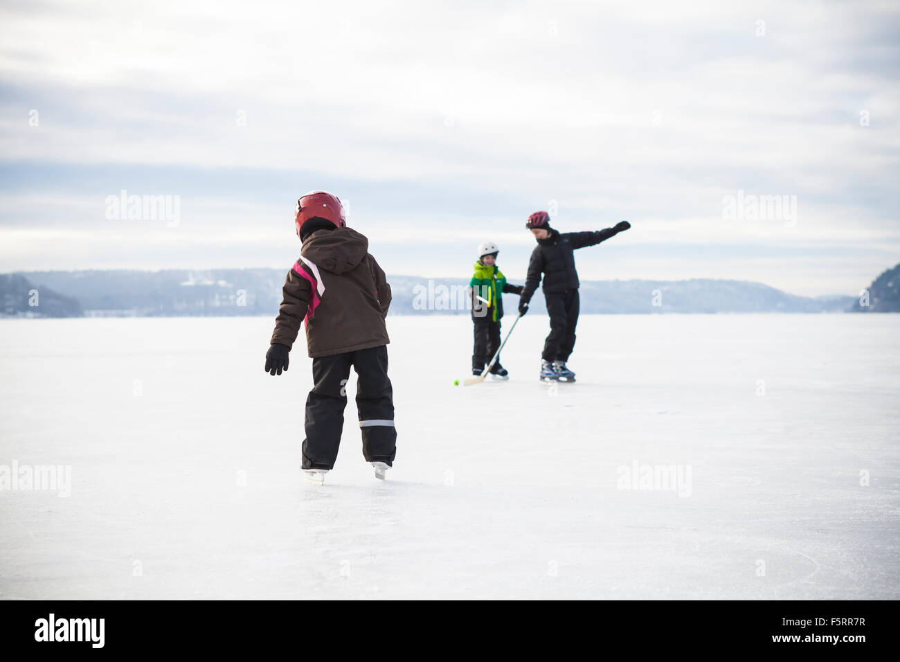 Sweden, Vastergotland, Lerum, Lake Aspen, Mom playing ice hockey with her two children (6-7, 8-9) on lake - Stock Image
