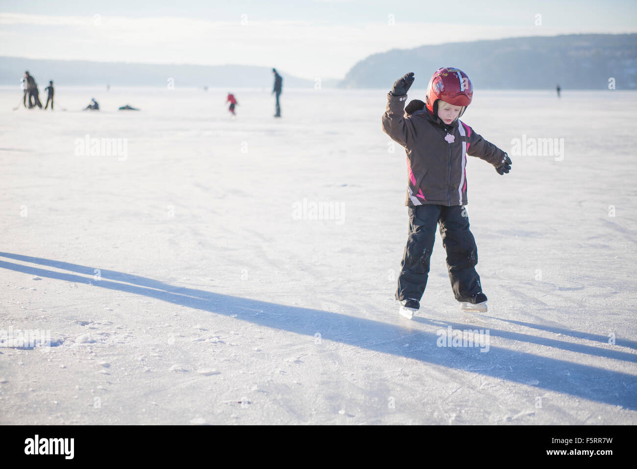 Sweden, Vastergotland, Lerum, Lake Aspen, Girl (4-5) learning how to ice skate on lake - Stock Image