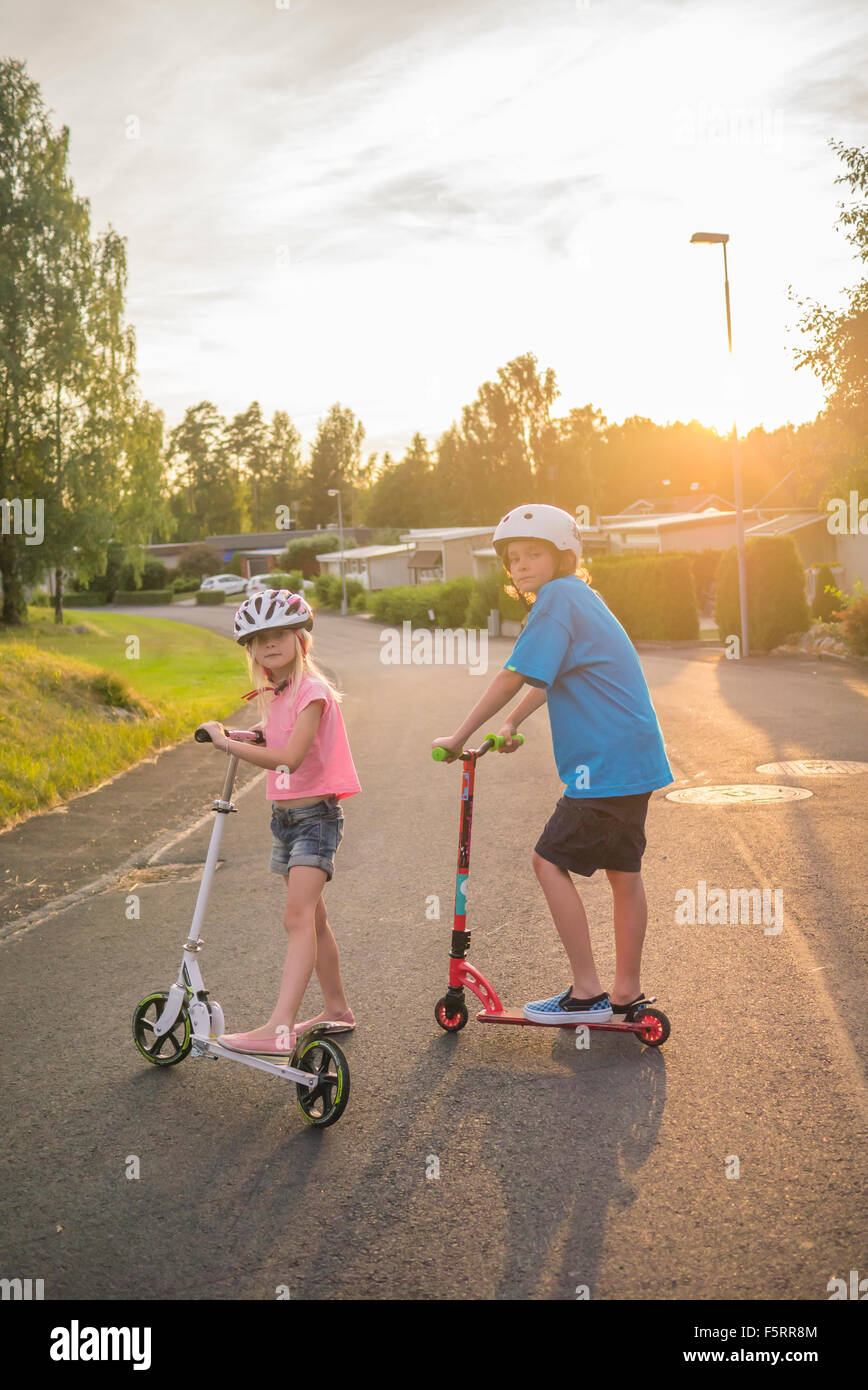 Sweden, Smaland, Anderstorp, Portrait of girl (8-9) and boy (10-11) posing with push scooters in town street - Stock Image