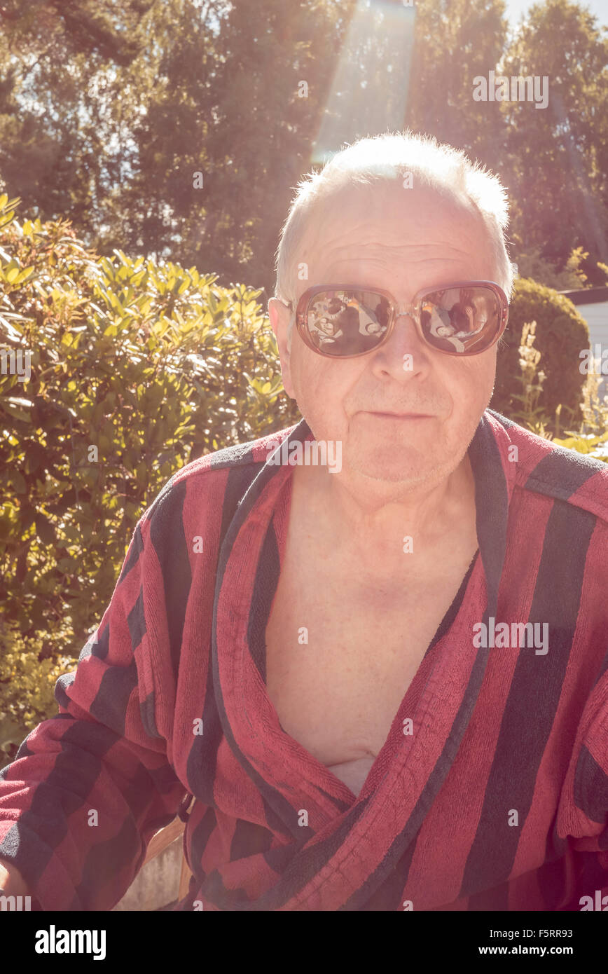 Sweden, Smaland, Anderstorp, Portrait of senior man wearing striped bathrobe and sunglasses - Stock Image
