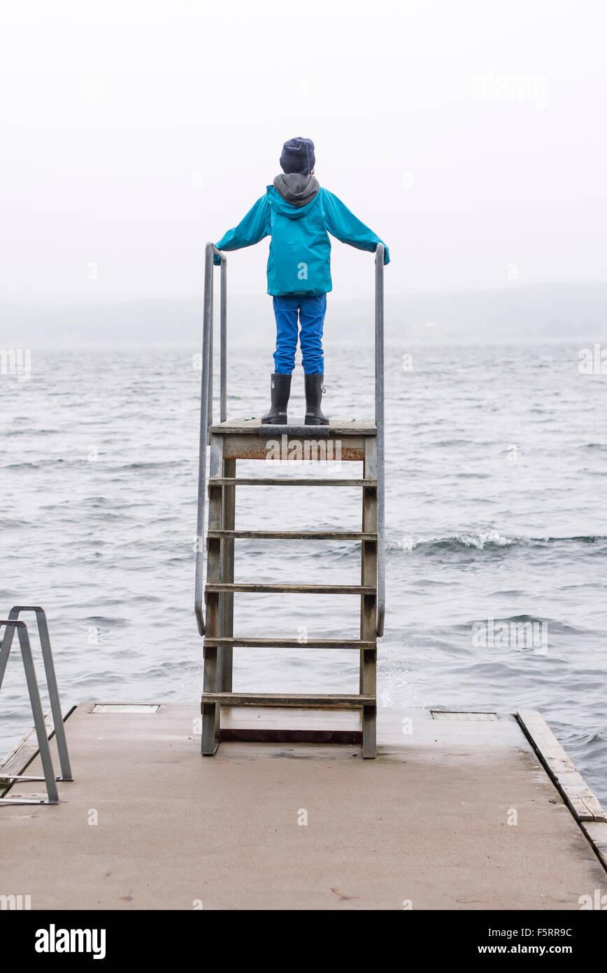 Sweden, Bohuslan, Halleback, Rear view of boy (10-11) standing on diving tower built on edge of pier - Stock Image