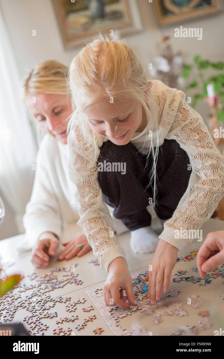 Sweden, Girl (8-9) making jigsaw puzzle - Stock Image