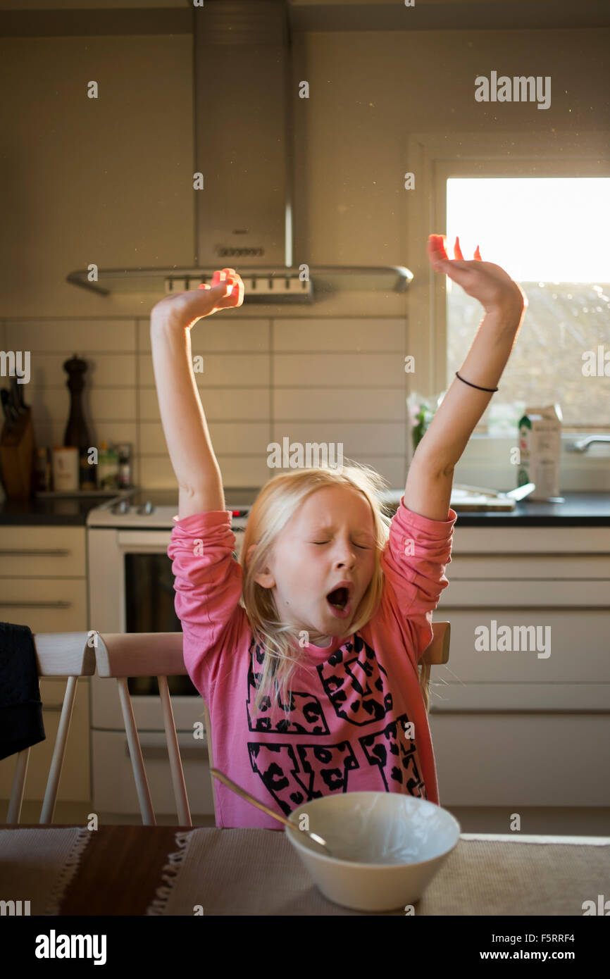 Sweden, Girl (10-11) yawning at table - Stock Image