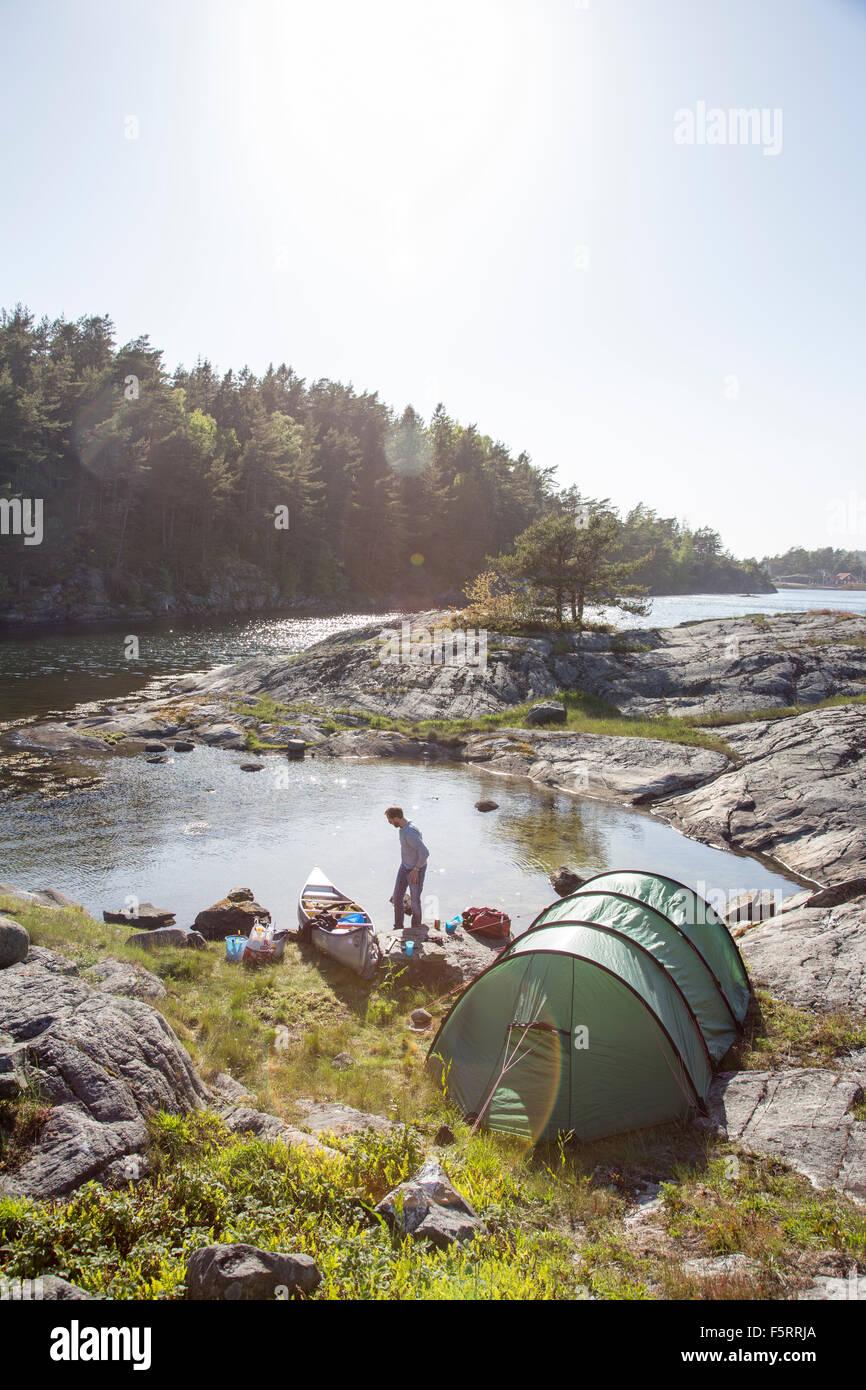Sweden, West Coast, Bohuslan, Flato, Man camping on riverbank - Stock Image