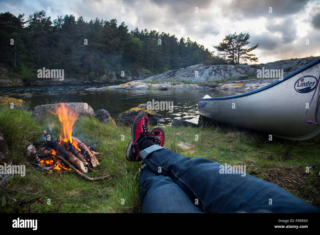 Sweden, West Coast, Bohuslan, Flato, Personal perspective of man lying by campfire on riverbank - Stock Image