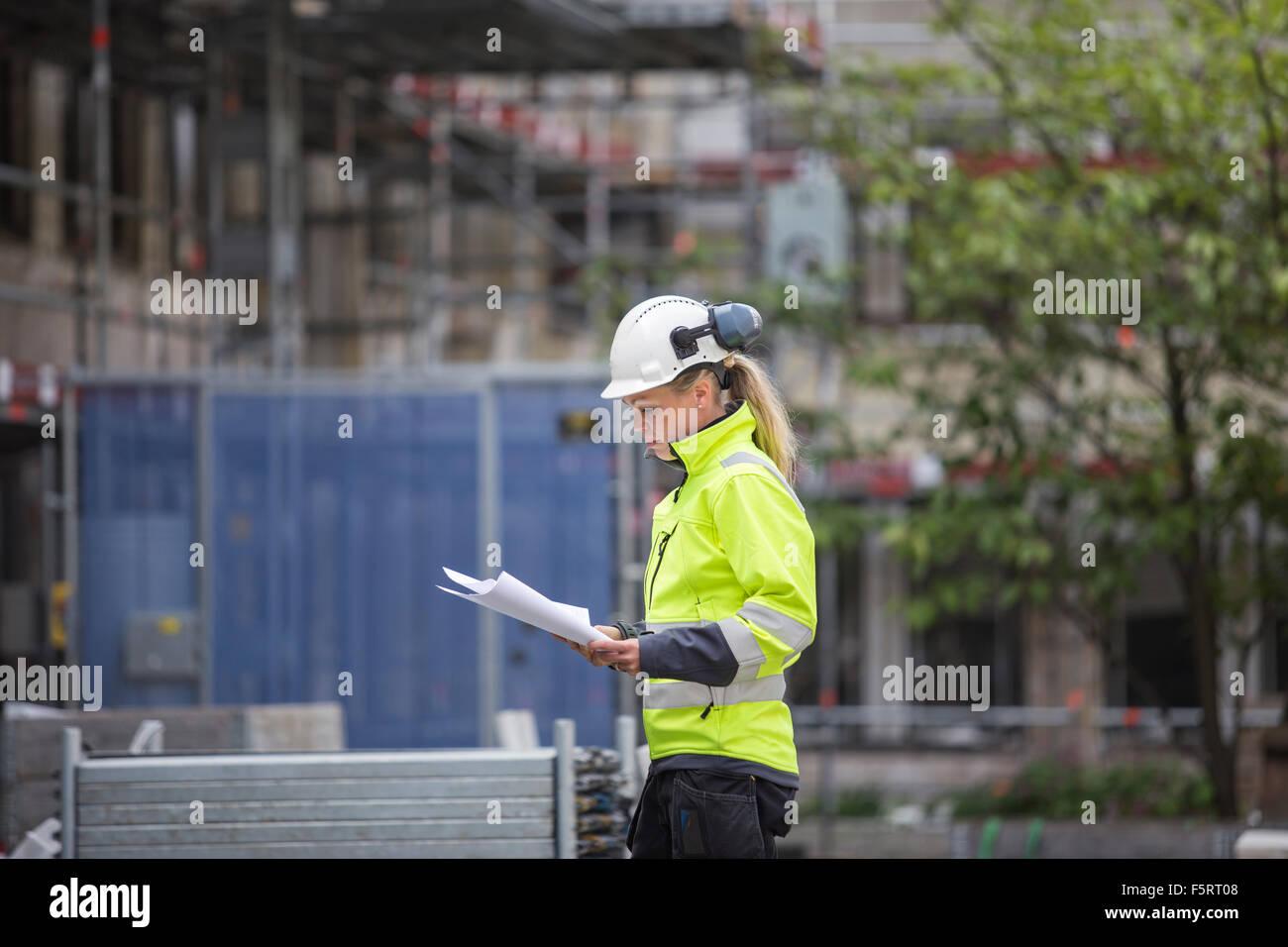 Sweden, Vastergotland, Construction worker looking at blueprints - Stock Image