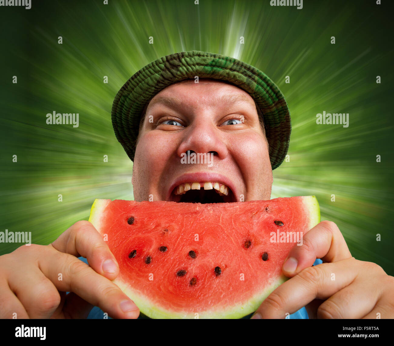 Bizarre man eating watermelon outdoors in summer - Stock Image