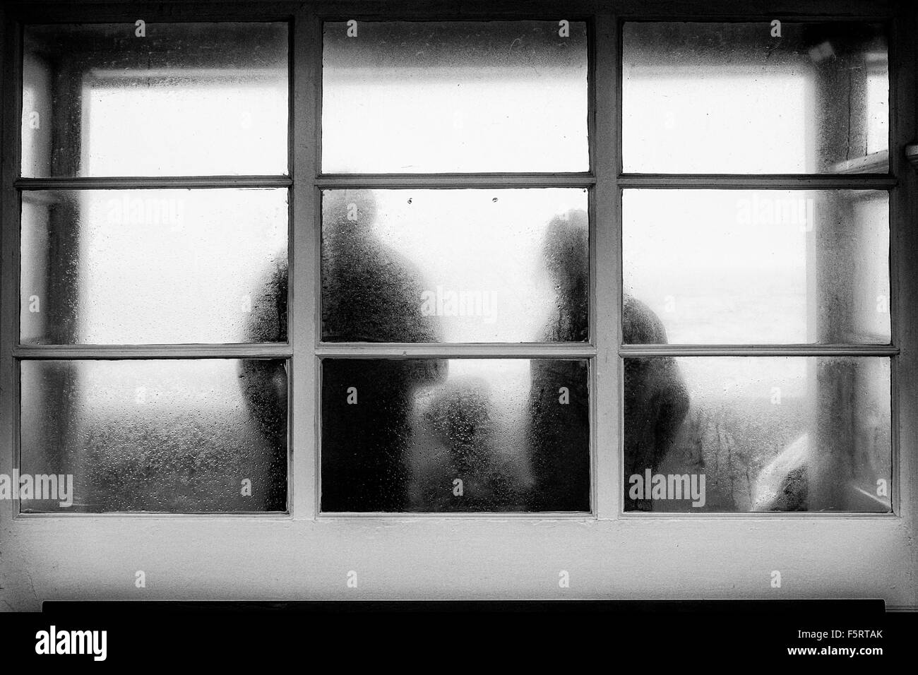 A family shelter from the rain in a seafront shelter, photographed through the wet frosted glass. Stock Photo