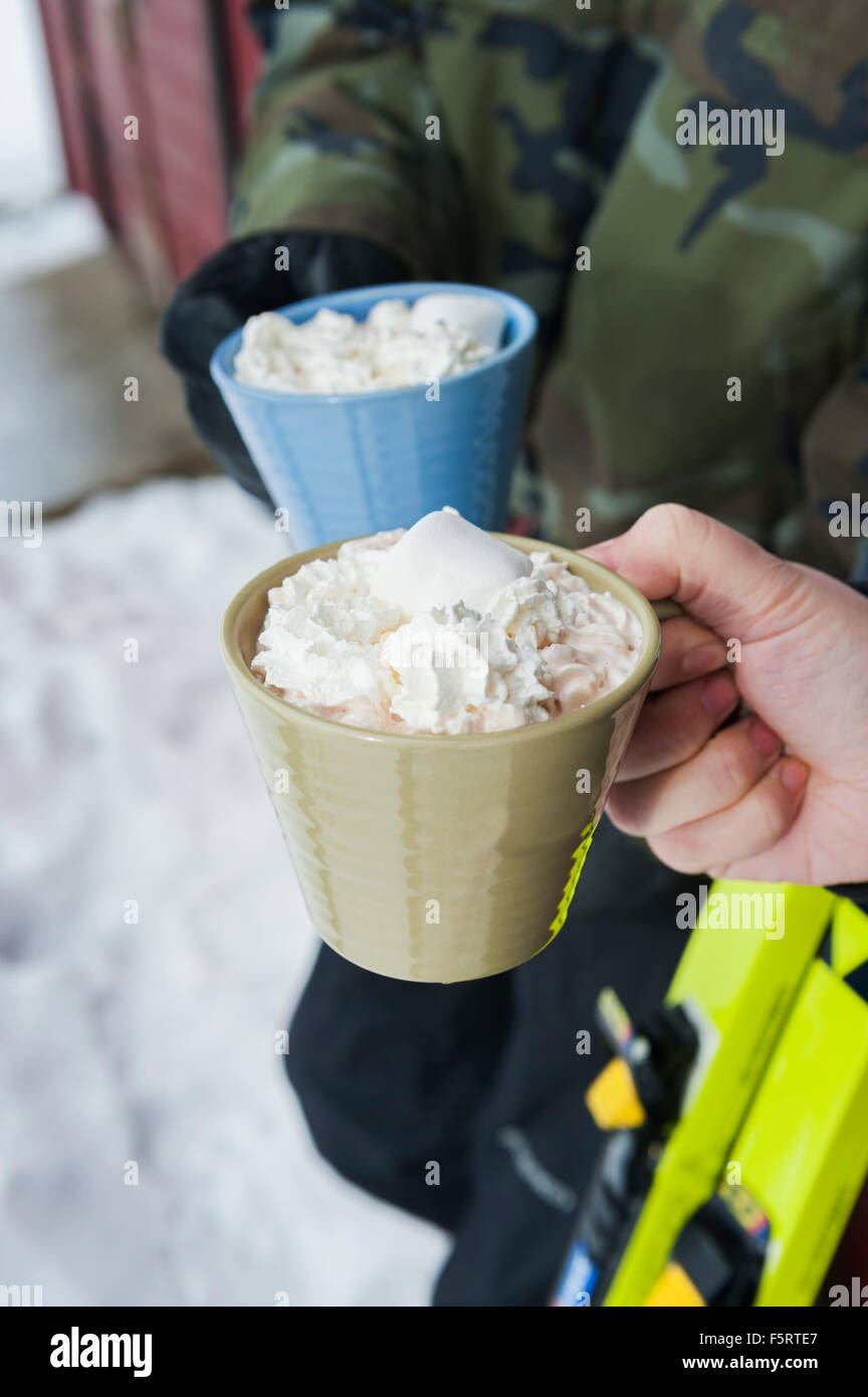 Sweden, Stockholm, Bjorkhagen, Hammarbybacken, Cropped view of man and woman holding mugs of hot chocolate with - Stock Image